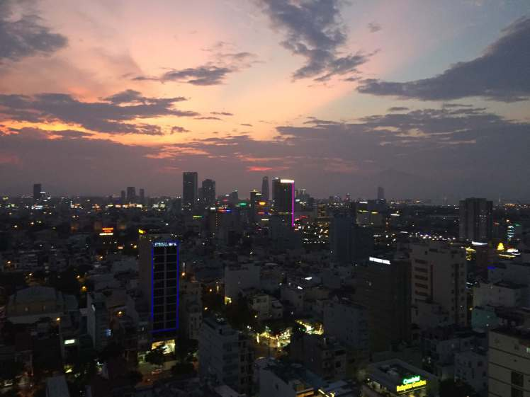 The neon skyline of Đà Nẵng beginning to flicker on in the evening.